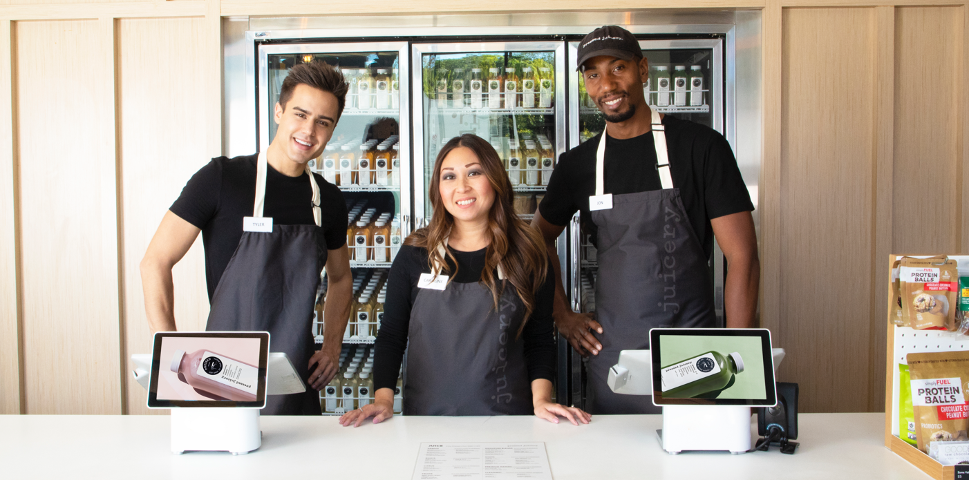 Three Pressed Juicery Employees standing in front of a Pressed Juicery fridge.