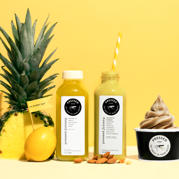 Pressed Juicery citrus 2, turmeric almond and vanilla freeze next to pineapple, lemon, and almonds on a yellow background